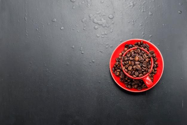 Tazza rossa e chicchi di caffè su uno sfondo nero,