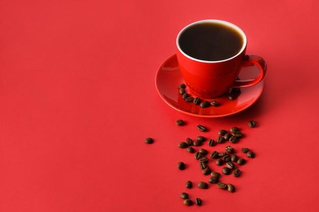 Tazza di caffè e fagioli rossi su fondo rosso. copia spazio. avvicinamento.