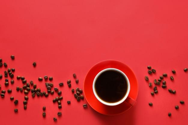 Tazza di caffè e fagioli rossi su fondo rosso. copia spazio. vista dall'alto.