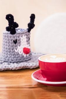 Tazza rossa di caffè cappuccino e grazioso cestino lavorato a maglia decorativo
