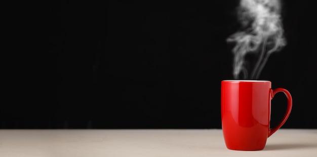 Tazza di caffè rossa su sfondo scuro