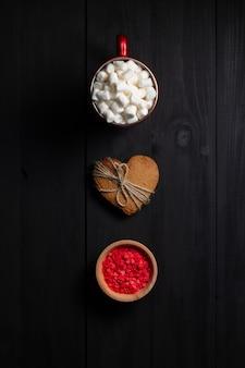 Tazza di caffè rossa con marshmallow, biscotto di pan di zenzero a forma di cuore e guarnizione di pasticceria. vista dall'alto