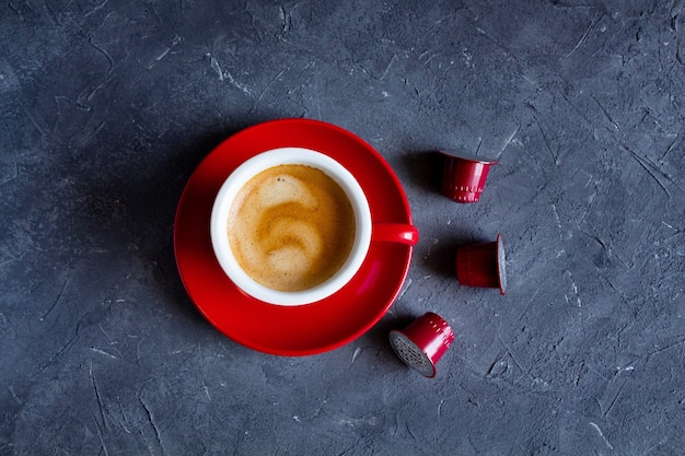 Tazza rossa di cappuccino caldo con capsule di caffè.
