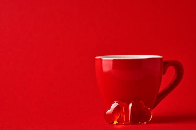 Tazza rossa e due cuori di cioccolato sul tavolo rosso o scarlatto. composizione piatta laica. concetto di san valentino. vista dall'alto, copia dello spazio.