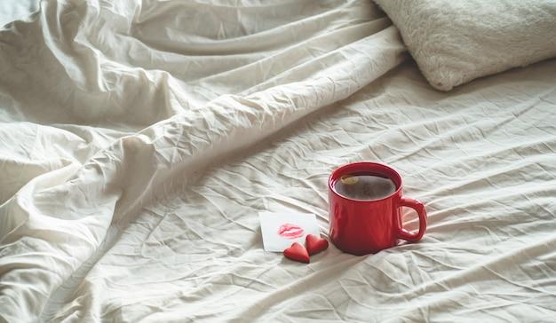 Tazza di tè rossa e due cuori di biscotti, una nota con un bacio su un letto bianco