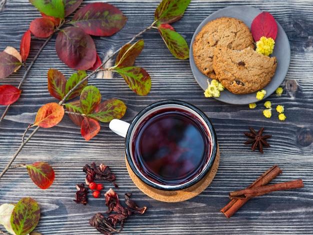 Tazza rossa di tè con il bastoncino di cannella, l'ostruzione ed i biscotti sull'umore di legno di autunno della tavola