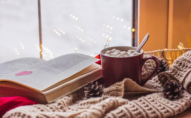 Tazza rossa con cacao e marshmallow su un tavolo in legno con sciarpe vecchio libro comfort domestico