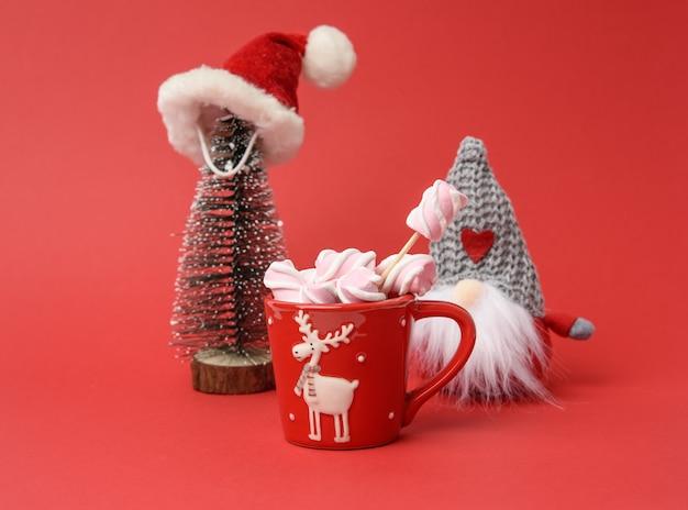 Tazza rossa con cioccolata calda e marshmallow e albero di natale in miniatura in cappello di babbo natale su uno sfondo rosso