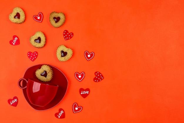 Tazza rossa con biscotti a forma di cuore di biscotti piattino e linzer su sfondo rosso. biglietto di auguri di san valentino