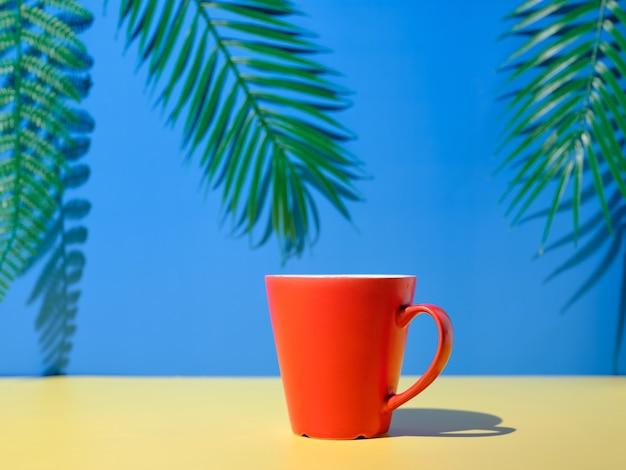 Tazza rossa sul tavolo giallo e sfondo blu con piante