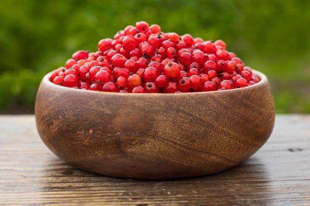 Ribes rosso in un piatto di legno su un tavolo in giardino. avvicinamento
