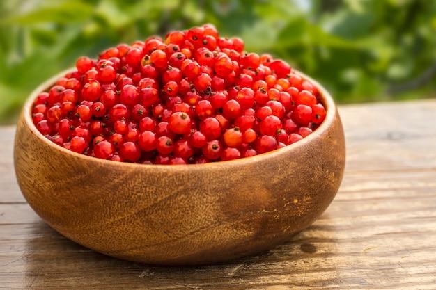 Ribes rosso in un piatto di legno su un tavolo in giardino. copia spazio