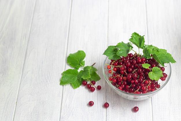 Ribes rosso su uno sfondo di legno chiaro. cocktail vitaminico.