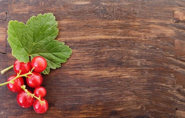 Ribes rosso con foglie su uno sfondo di legno.