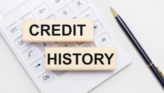 La cartella documenti rossa dice credit history accanto al caffè, alla calcolatrice e alla penna.