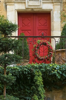 Porta rossa con natale con ghirlanda di rami e coni di albero di natale