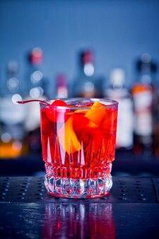 Cocktail rosso della bevanda in vaso di vetro con la ciliegia e la buccia d'arancia sulla tavola di legno nel bar