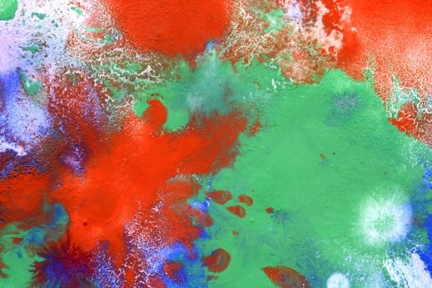 Gocce rosse, macchie verdi blu sulla superficie da vicino