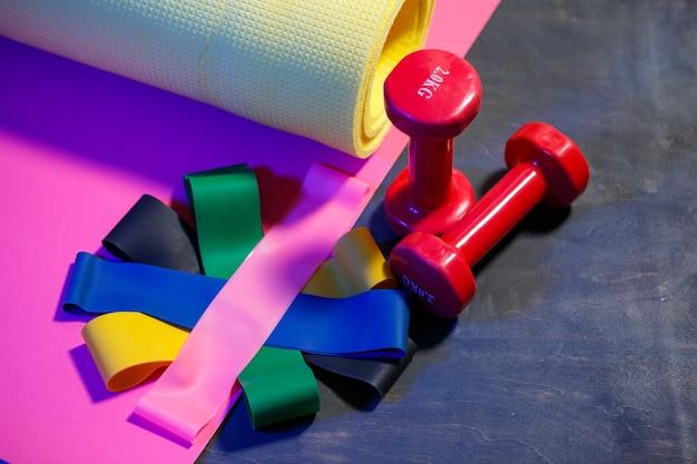 Manubri rossi, tappetino fitness e elastici per lo sport su sfondo rosa. uno stile di vita sano. attrezzi fitness per allenamento con i pesi. sviluppo muscolare e allenamento fitness
