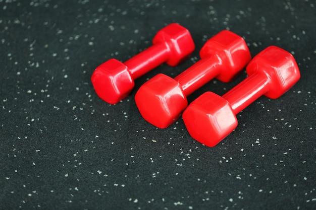 Manubri rossi sul pavimento in palestra