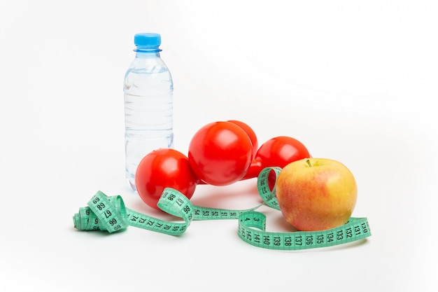 Manubri rossi, mela fresca, metro a nastro o metro a nastro e una bottiglia naturale di acqua frizzante su uno spazio bianco. concetto di uno stile di vita sano, fitness, dieta