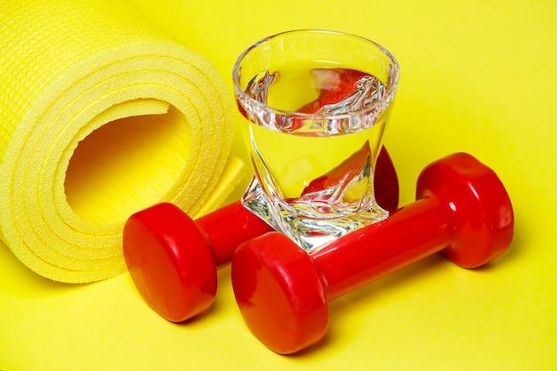 Manubri rossi, un bicchiere d'acqua, un tappeto giallo, sfondo colorato, sport, bevanda energetica, attrezzatura per la palestra