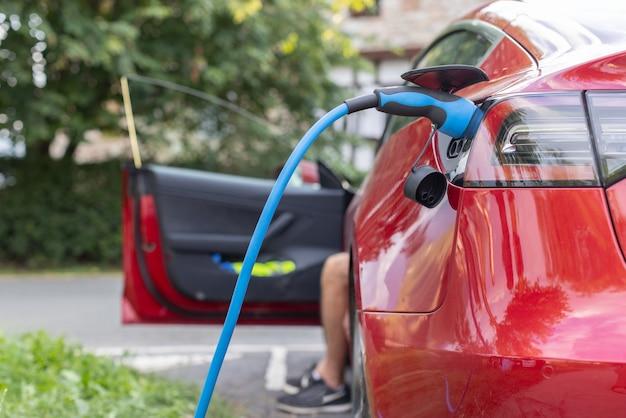 Auto elettrica rossa in attesa di essere caricata in un parcheggio mentre l'autista attende all'interno dell'auto. energia rinnovabile e concetto di sostenibilità