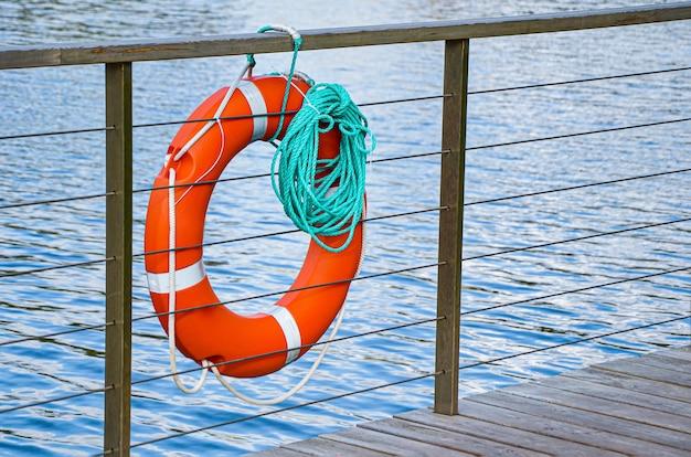 Salvagente di emergenza rosso con corda turchese sul molo vicino al mare. primo piano del salvagente sul molo. attrezzatura di salvataggio per emergenza in acqua.