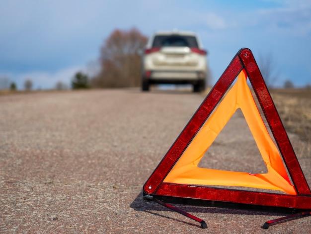 Segnale di arresto di emergenza rosso. sullo sfondo, l'auto si è fermata e le luci di emergenza lampeggiano. concetto di incidenti, guasti, servizi di assistenza