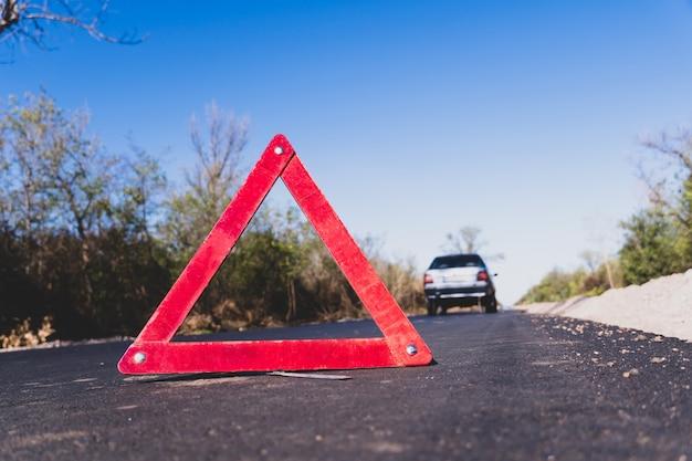 Segnale di arresto di emergenza rosso vicino sulla strada sullo sfondo di un'auto distrutta grigia