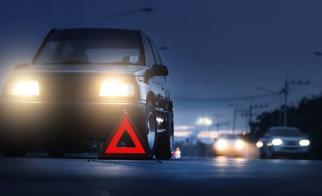 Segnale di arresto di emergenza rosso (segnale di avvertimento triangolo rosso) e auto suv nera rotta su strada di campagna, nebbia selettiva su auto suv