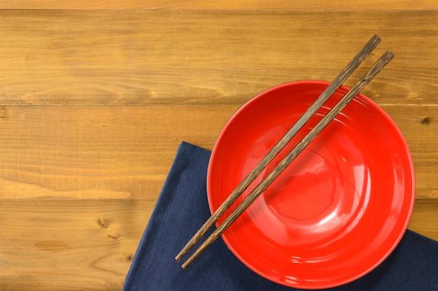 Ciotola vuota rossa con le bacchette sulla tavola di legno e sulla tovaglia blu scuro