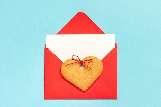 La busta rossa con la carta bianca in bianco per testo e cuore ha modellato i biscotti dello zenzero sul blu