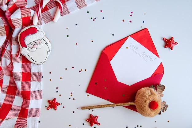 Busta rossa con una lettera a babbo natale, un tovagliolo in gabbia e una penna