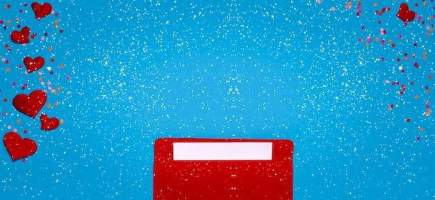 Busta rossa con lettera d'amore sopra sfondo blu con molti cuori intorno e fiocchi di neve. i cuori fuoriescono dalla busta. lettera d'amore. concetto di amore