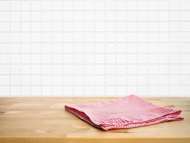 Tessuto rosso, panno sul piano del tavolo in legno su sfocatura sfondo bianco muro di mattoni