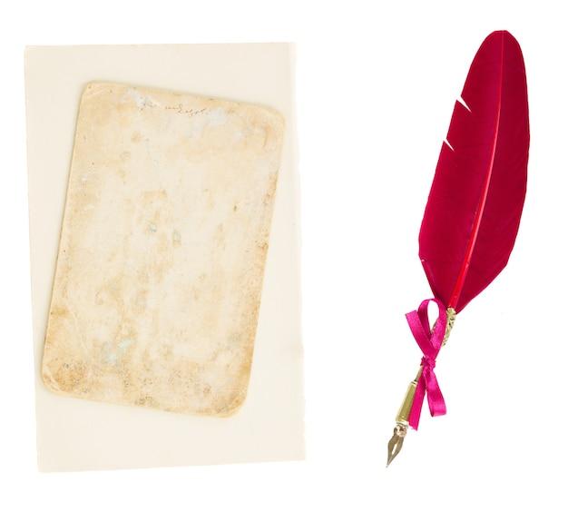 Penna piuma rossa con la vecchia pagina isolata su bianco