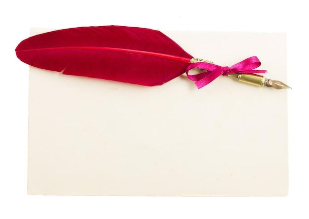 Penna piuma rossa con pagina di carta isolato su bianco