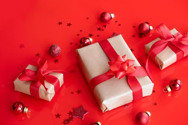 Contenitore di regali rosso sfondo festivo con stelle lucenti e palloncini vista dall'alto.