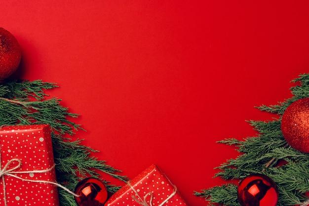 Decorazioni natalizie festive rosse con rami di conifere
