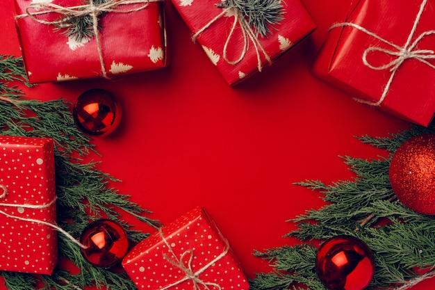 Natale festivo rosso con rami di conifere