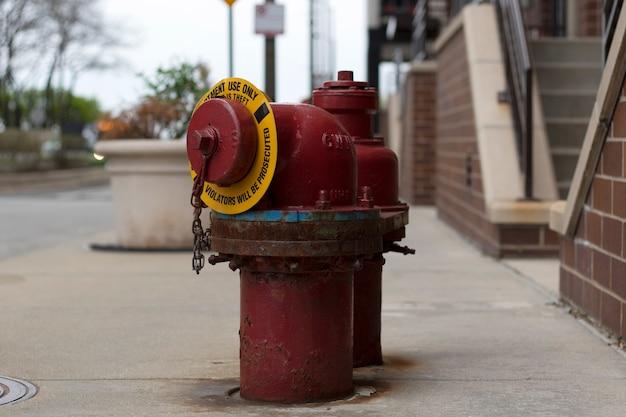 Un idrante antincendio rosso seduto sul marciapiede
