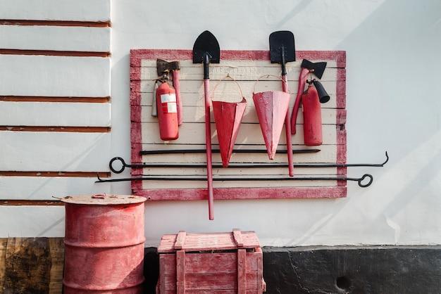 Scudo antincendio rosso con strumenti antincendio