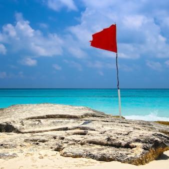Bandiera rossa sulla spiaggia di cancun Foto Premium