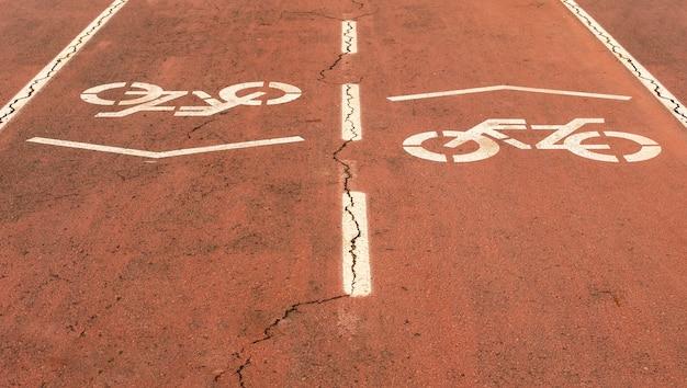 Pista ciclabile a pavimento rosso con simbolo di priorità bicicletta