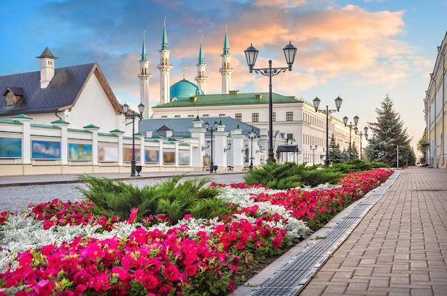 Fiori rossi sul territorio del cremlino di kazan e della moschea kul-sharif sotto un bellissimo cielo al tramonto