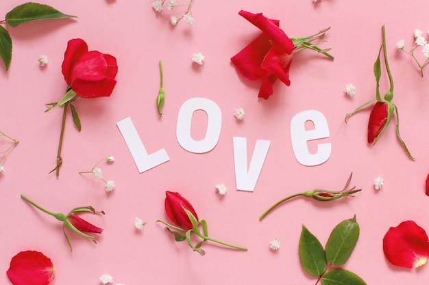 Fiori rossi e testo amore su una vista dall'alto di sfondo rosa chiaro