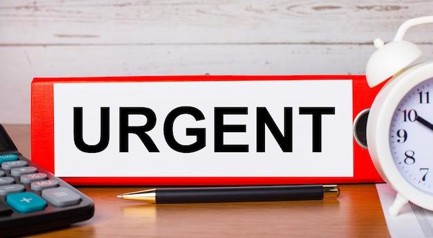 Cartella rossa per documenti con il testo urgente, sveglia bianca, calcolatrice e penna sul desktop. concetto di affari