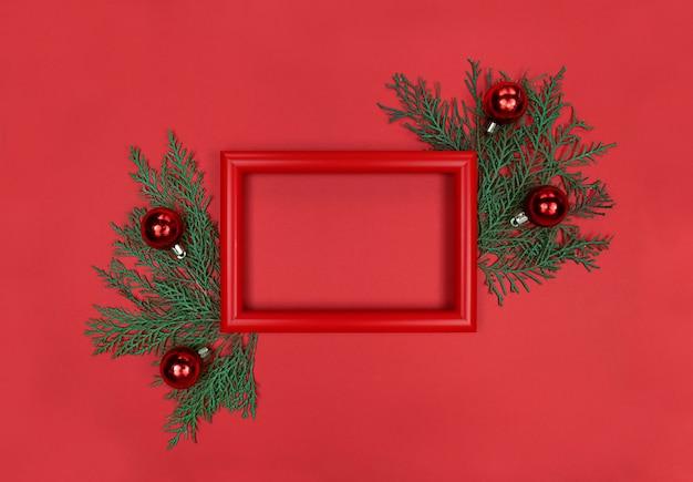 Cornice rossa, rami degli alberi e palline decorative. natale piatto monocromatico laici con copia spazio.