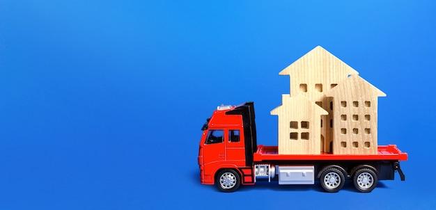 Camion merci rosso caricato con case di figura.